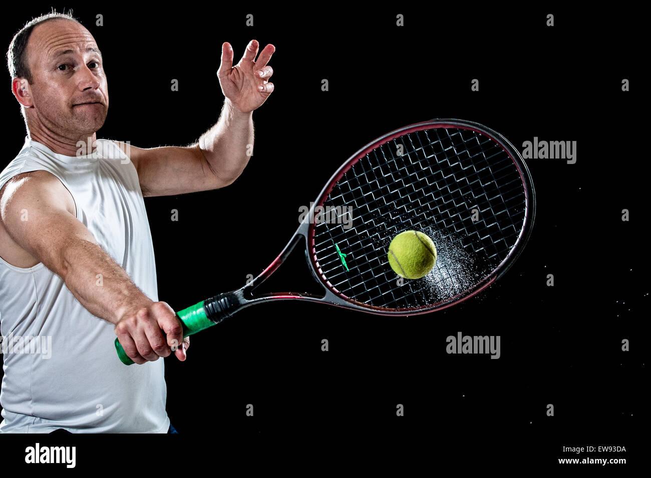 Tennis action shot. Backhand. Studio shot over black. - Stock Image