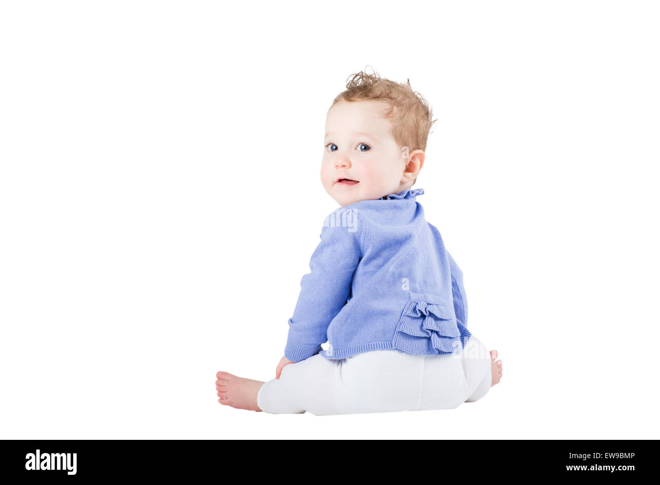 Sweet baby girl sitting and watching over her shoulder, isolated on white - Stock Image