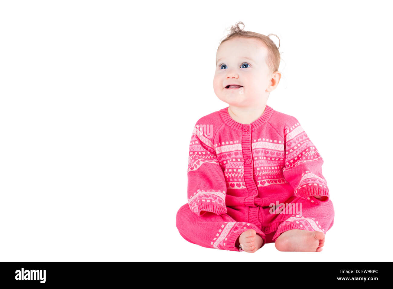 Sweet baby girl in a pink sweater with hearts pattern, isolated on white - Stock Image