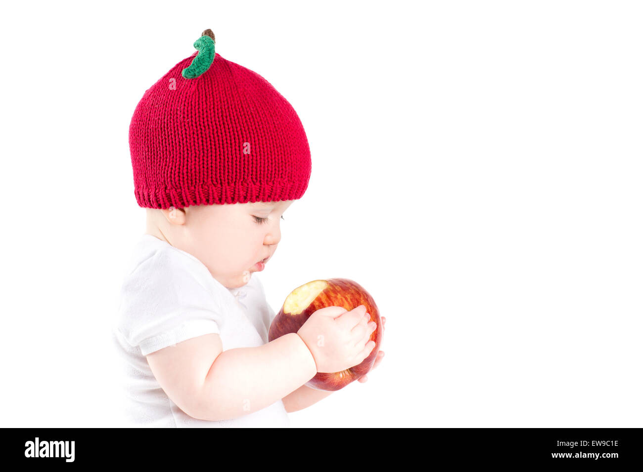 Funny little baby in an apple hat holding a big red apple, isolated on white - Stock Image
