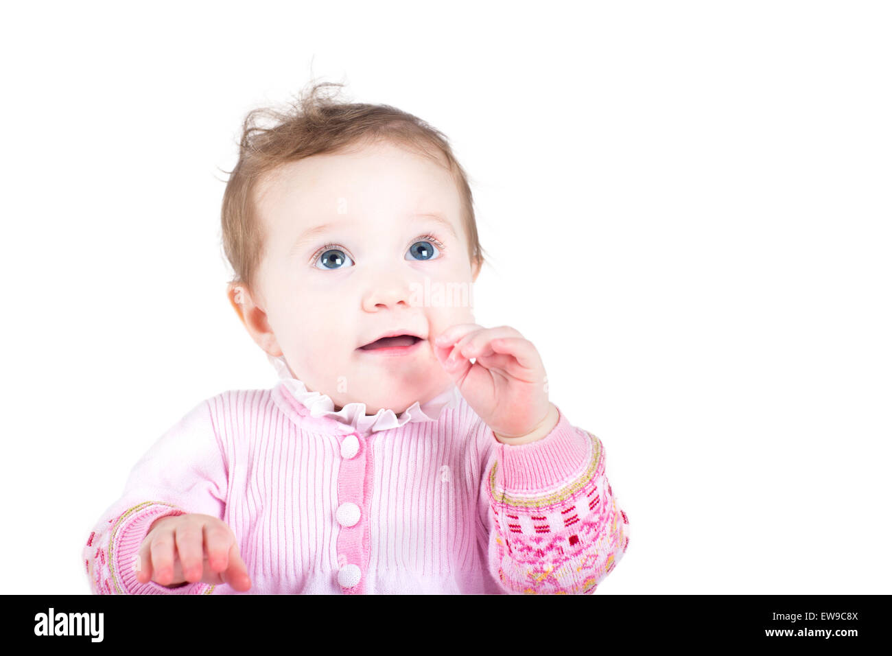 Beautiful baby girl in a pink knitted jacket, isolated on white - Stock Image