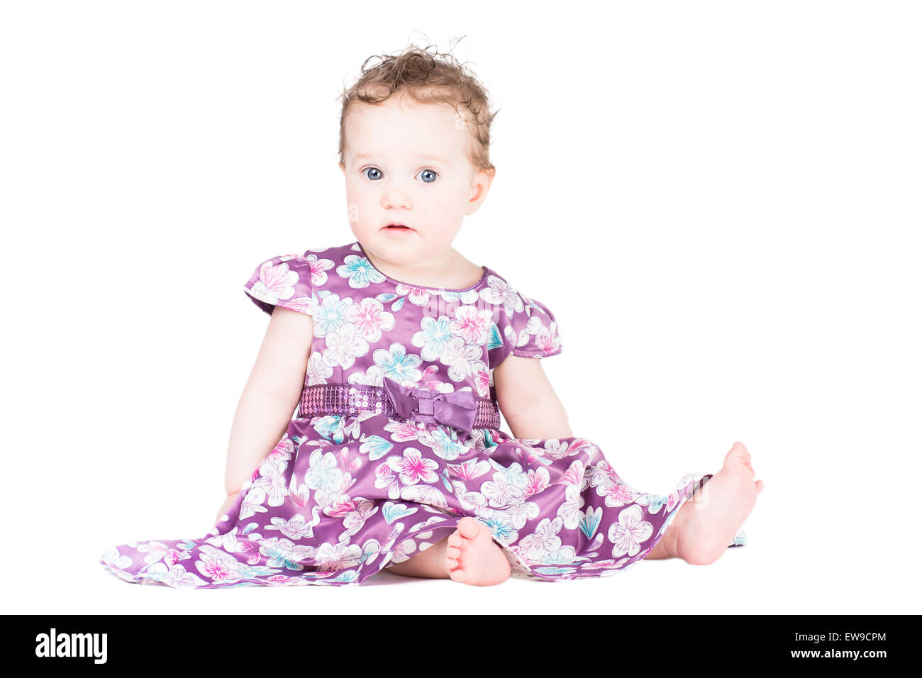 Sweet little baby girl in a festive purple dress, isolated on white - Stock Image