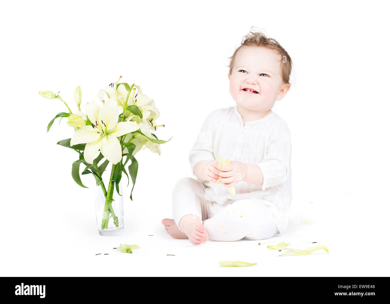 Funny little baby playing with lily flowers, on white - Stock Image
