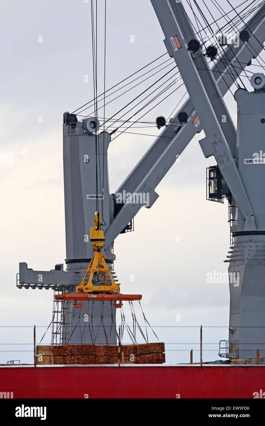 Cranes hoist lumber for export on board a freighter, Nanaimo, Vancouver Island, BC - Stock Image