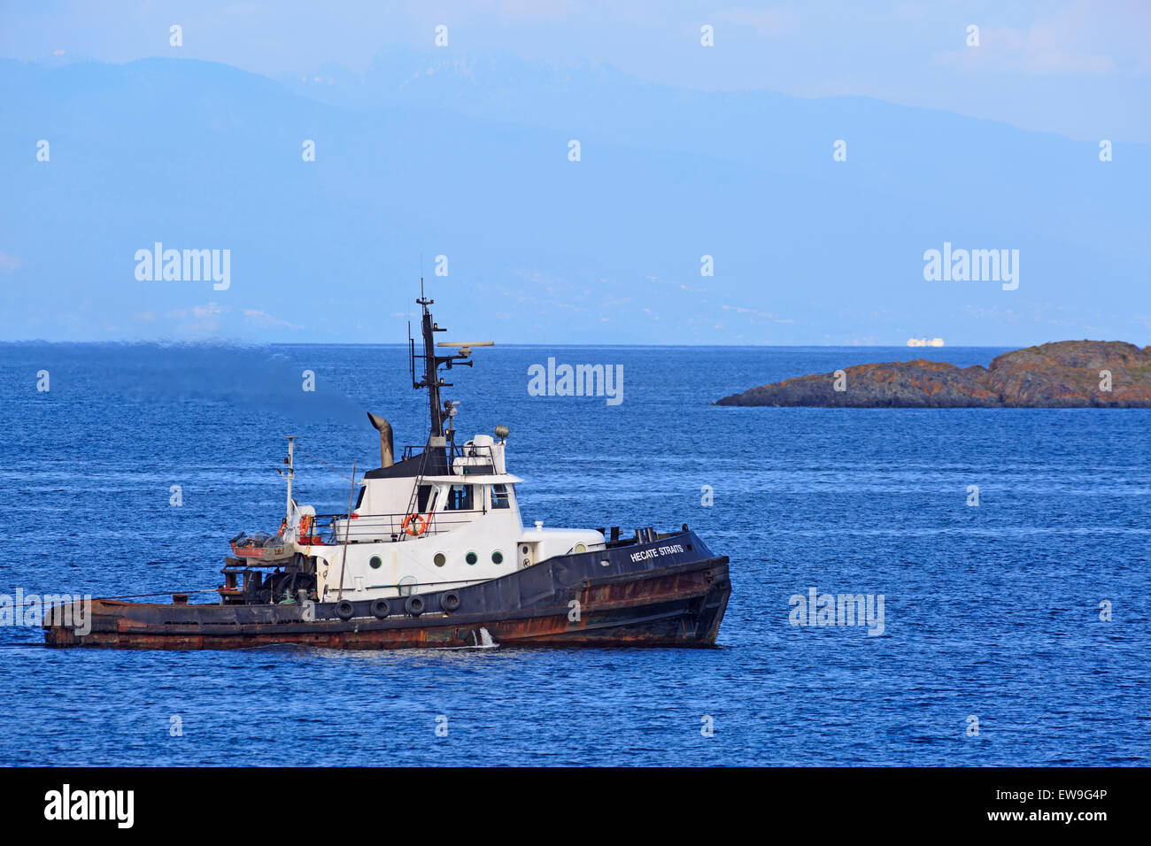 Tugboat pulling log boom in Georgia Strait, just north of Nanaimo, British Columbia - Stock Image