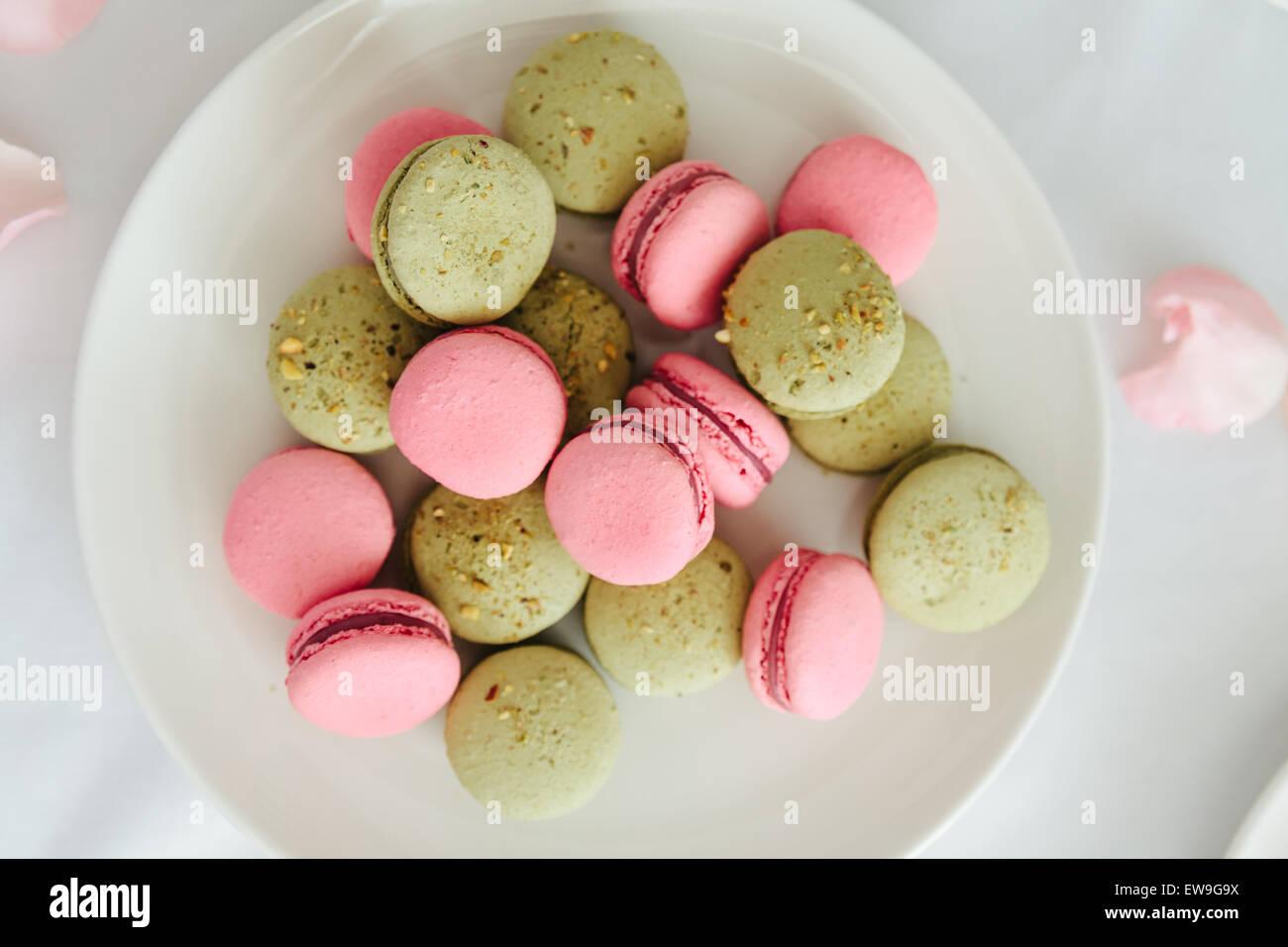 Fresh macarons on white plate - Stock Image