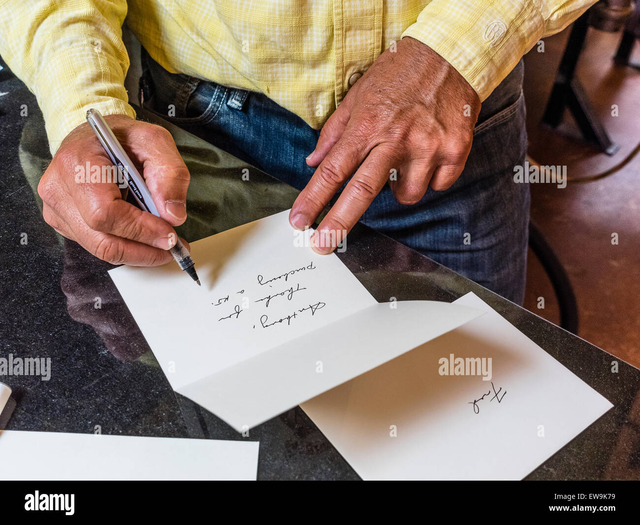 A man with weathered hands writes a thank you note in beautiful cursive writing to a customer who purchased one - Stock Image