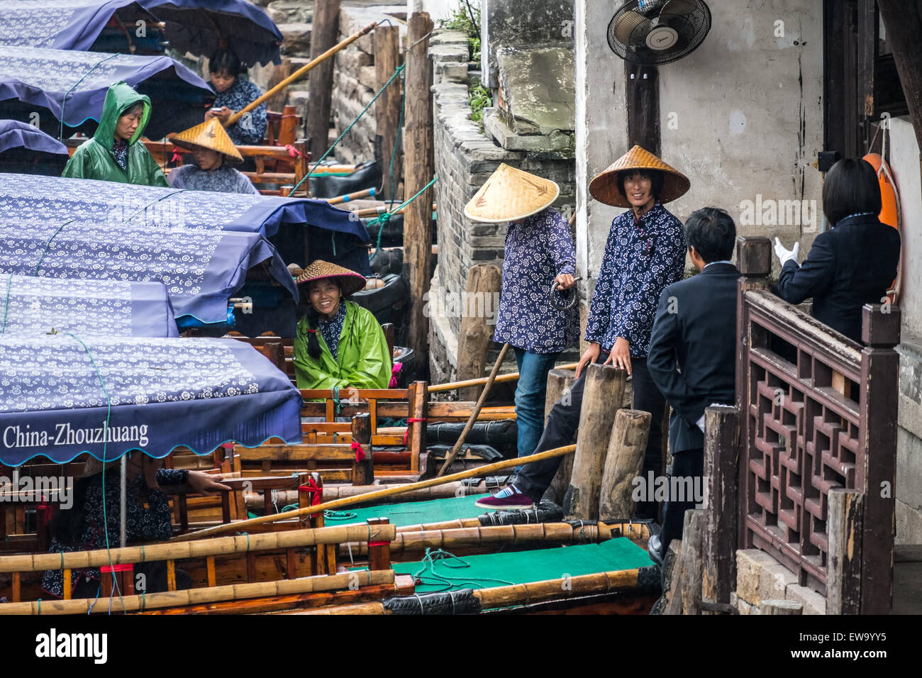 Boaters in raincoats on crowded dock - Stock Image
