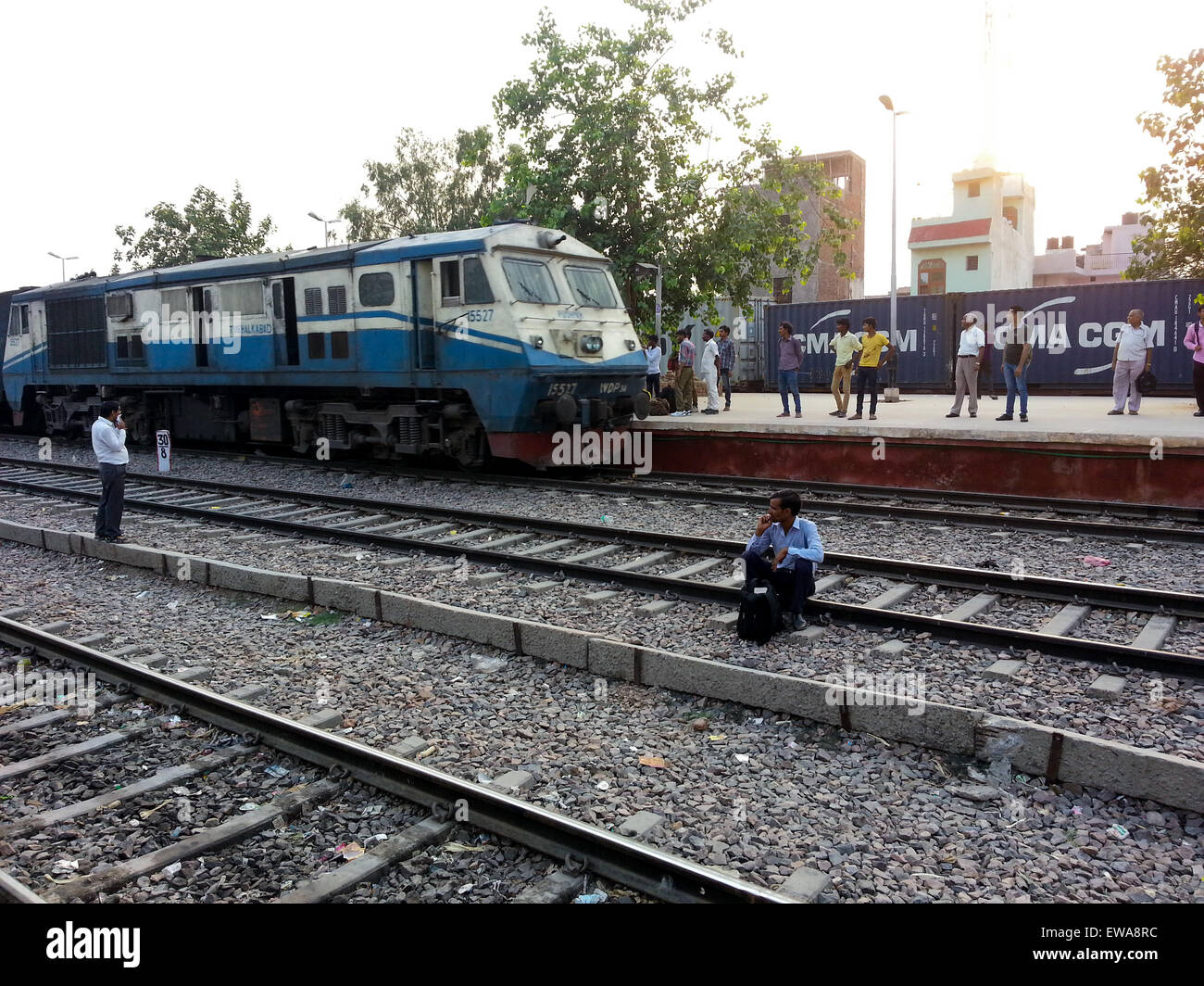 Gurgaon, India; 19th Jun'15: People waiting on the tracks as a train arrives at the Gurgaon station. Unsafe practices Stock Photo