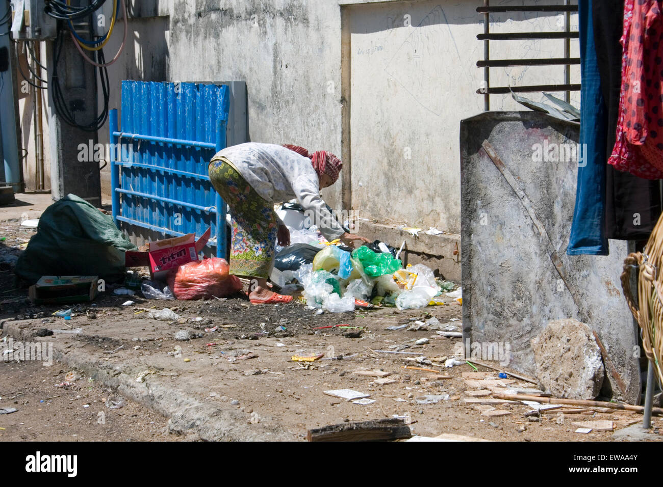 An elderly woman is scavenging through plastic for recyclable material on a city street in Kampong Cham, Cambodia. - Stock Image