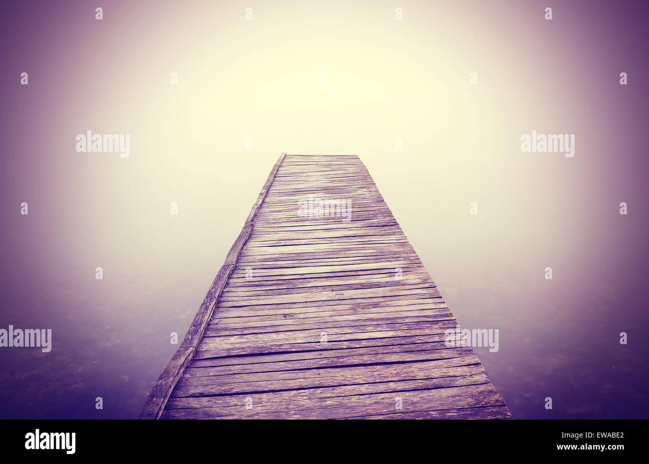 Vintage filtered picture of old wooden pier in dense fog with strong vignette effect. - Stock Image