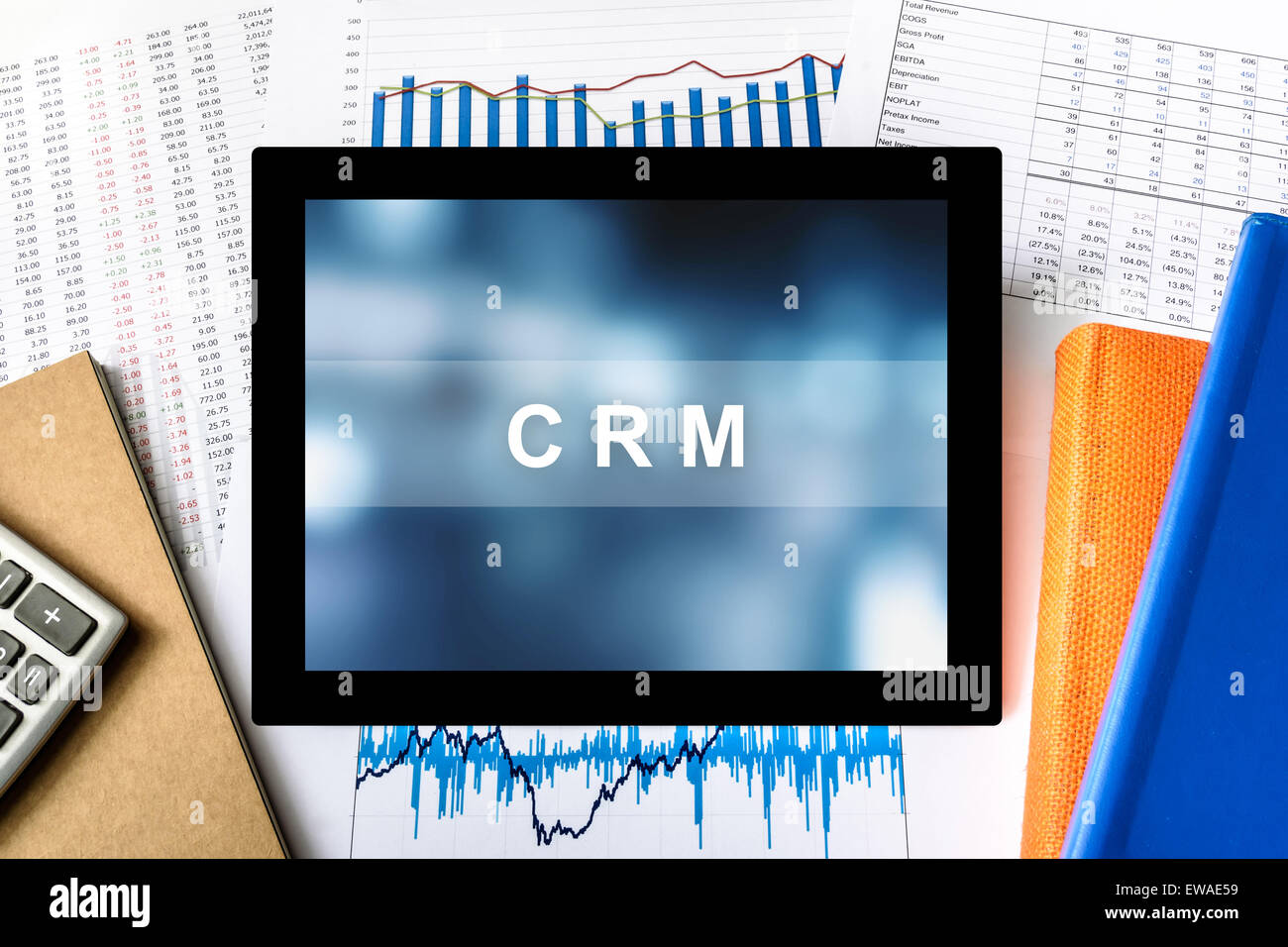 CRM or Customer relationship management word on tablet with financial graph background - Stock Image