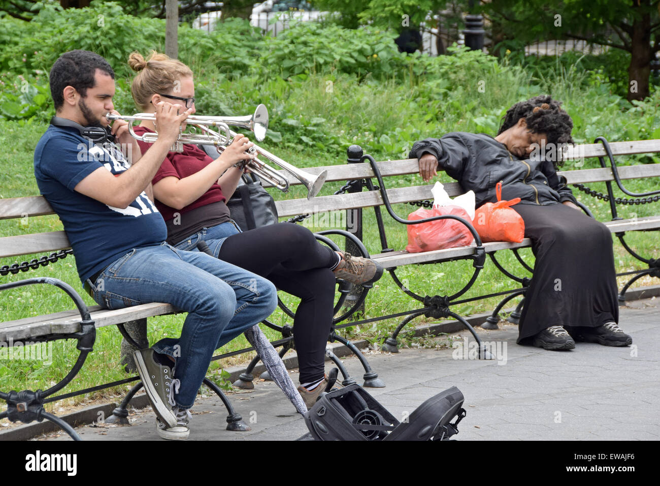 A young man and woman play their trumpets in Washington Square Park in NY while a sleeping woman is oblivious to - Stock Image
