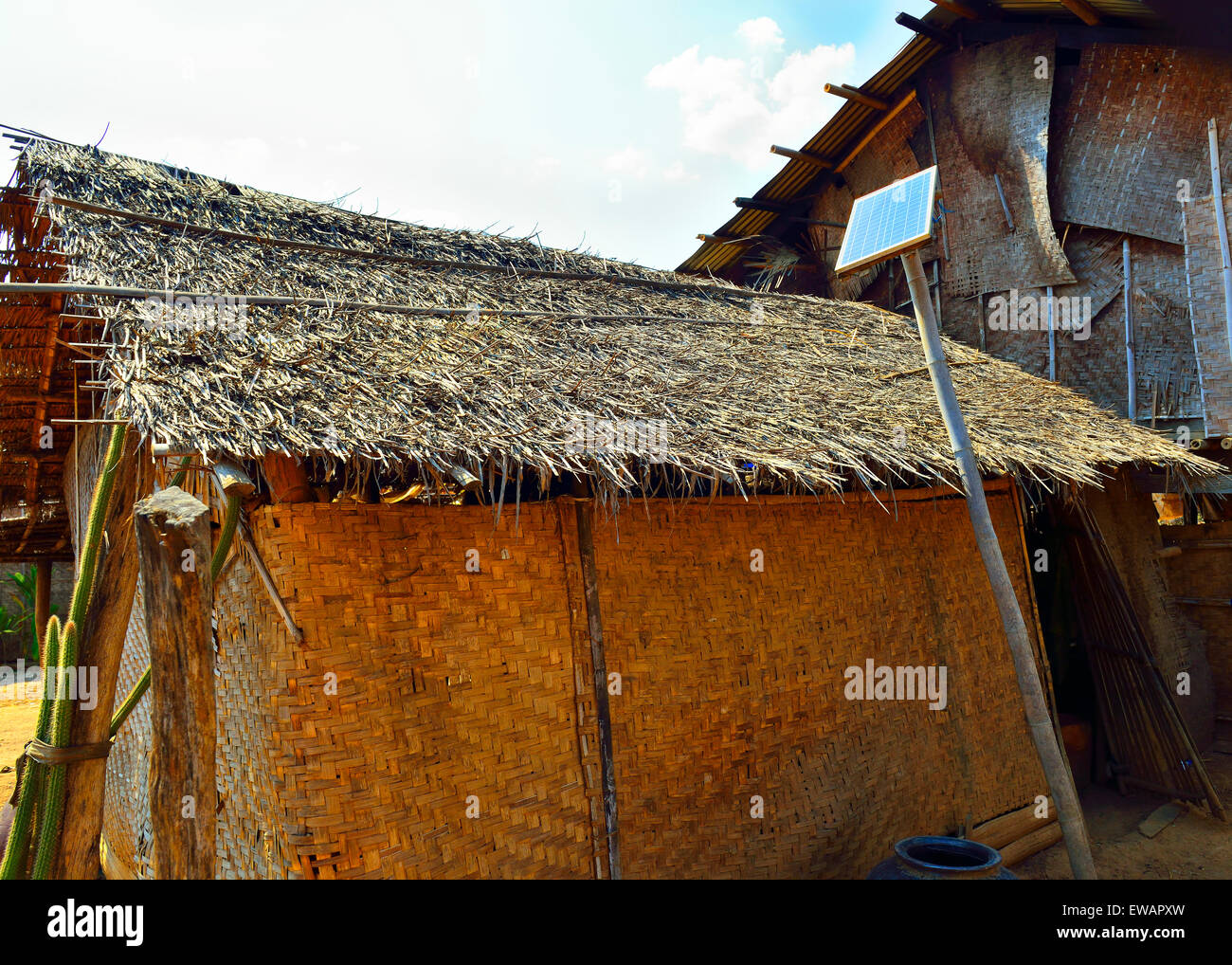 A single solar panel provides basic electricity for dwelling such as for a few lights bulbs only in village on Inle - Stock Image