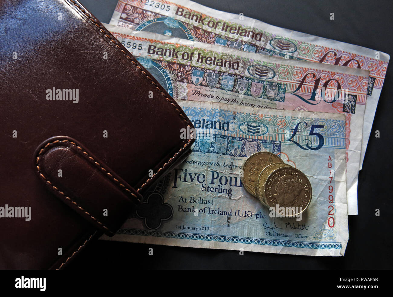 Northern Irish £5, £10 notes and pound coins, legal tender from the Bank Of Ireland  Belfast, next a wallet - Stock Image