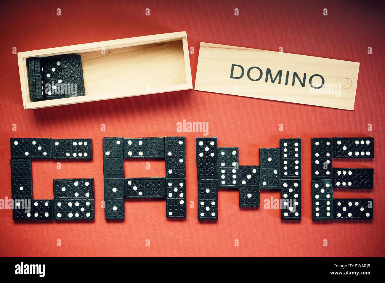 Word game written of dominoes on red background. - Stock Image