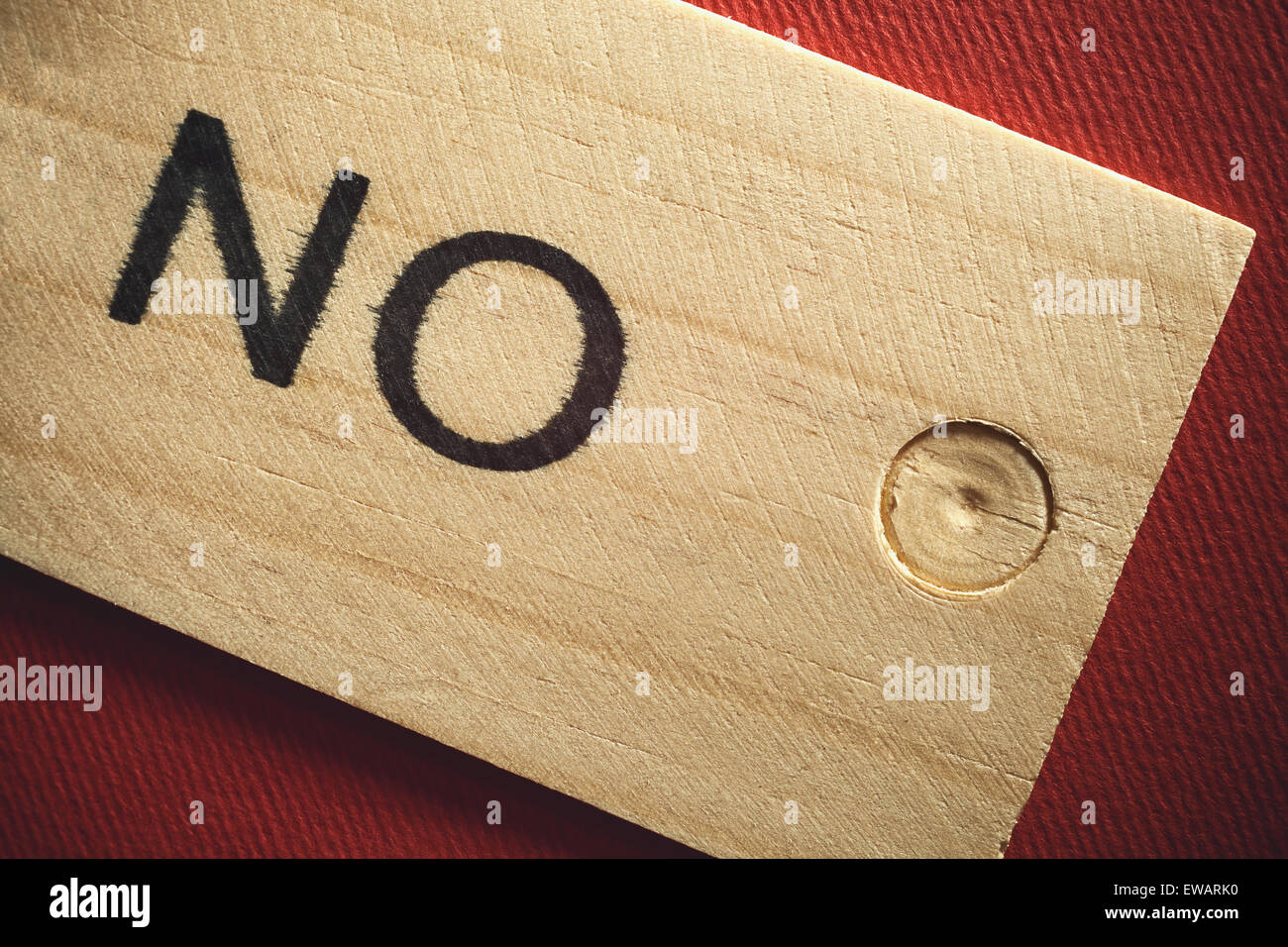 Word no written on wooden tile, red textured background. - Stock Image