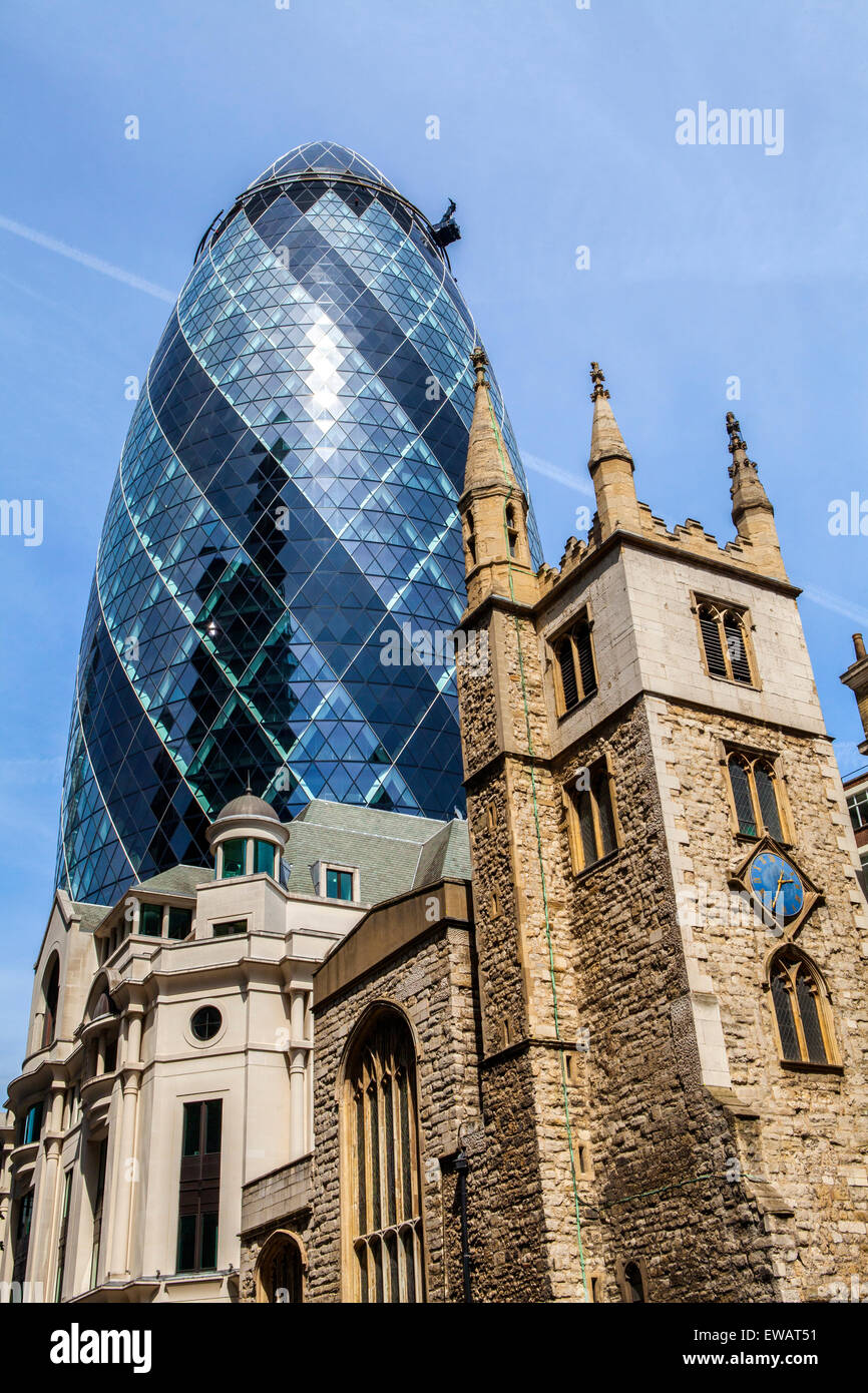 The historic St. Andrew Undershaft Church with 30 St. Mary Axe towering above it in the City of London. - Stock Image