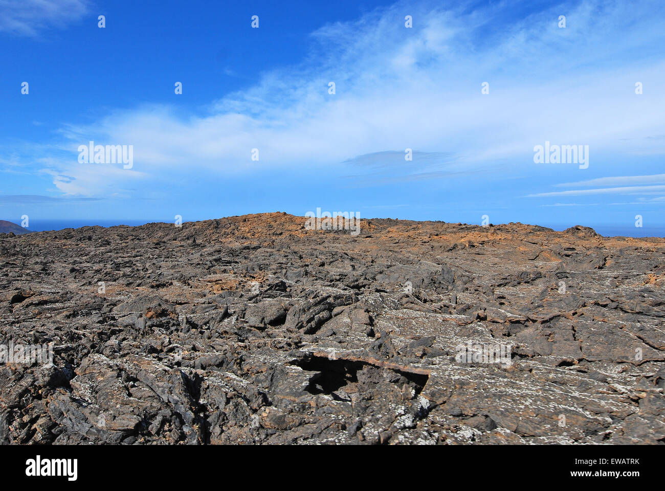 Lanzarote, Canary Islands, Spain. A lava field with mountains in the horizon, in Timanfaya Natural Park. - Stock Image