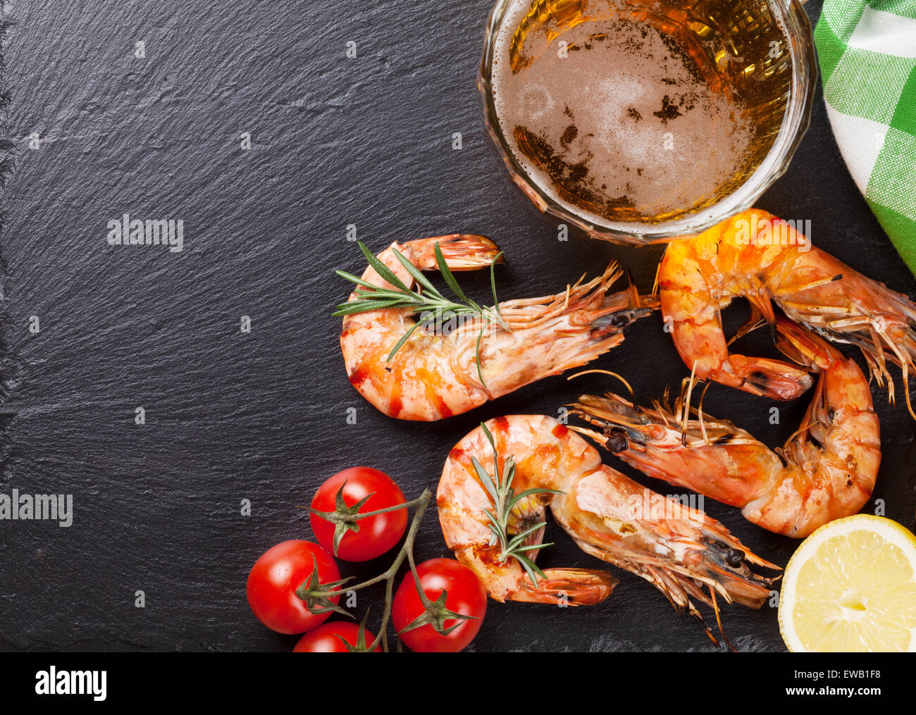 Beer mug and grilled shrimps on stone plate. Top view with copy space - Stock Image