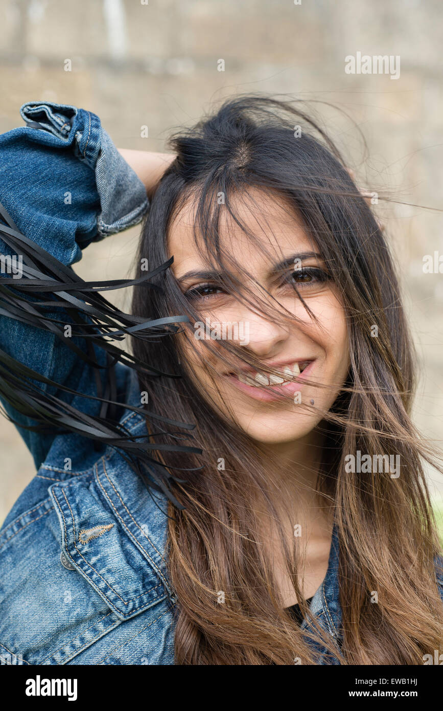 Portrait of a young brunette woman outdoors. The woman is smiling and has tousled hair - Stock Image