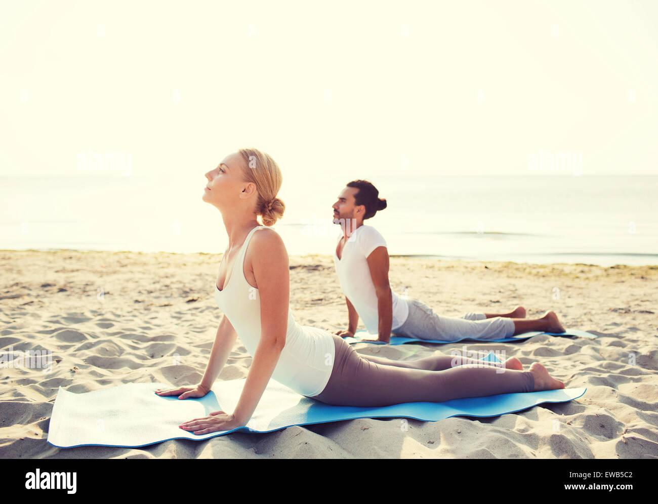 couple making yoga exercises outdoors - Stock Image