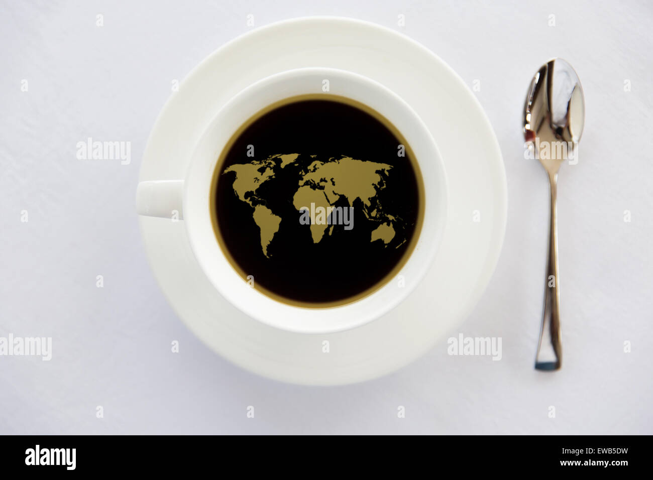 world map in cup of black coffee with spoon - Stock Image