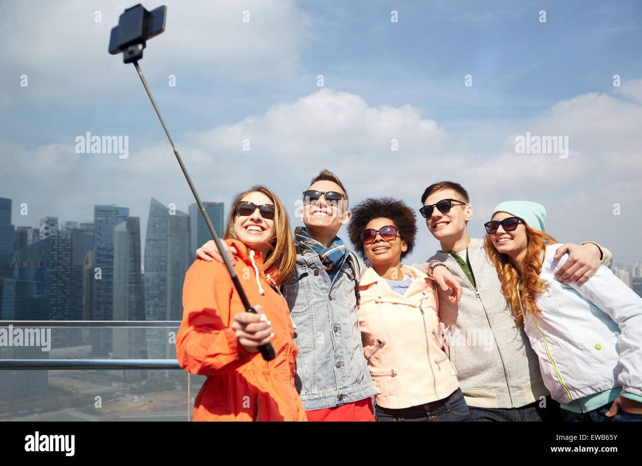 smiling friends taking selfie with smartphone - Stock Image