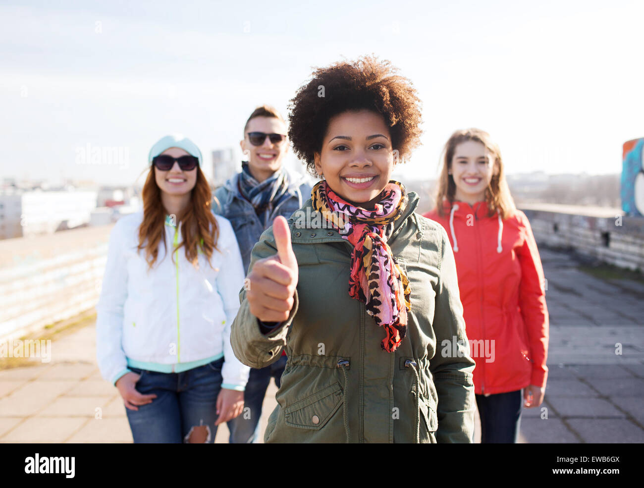 happy teenage friends showing thumbs up on street - Stock Image