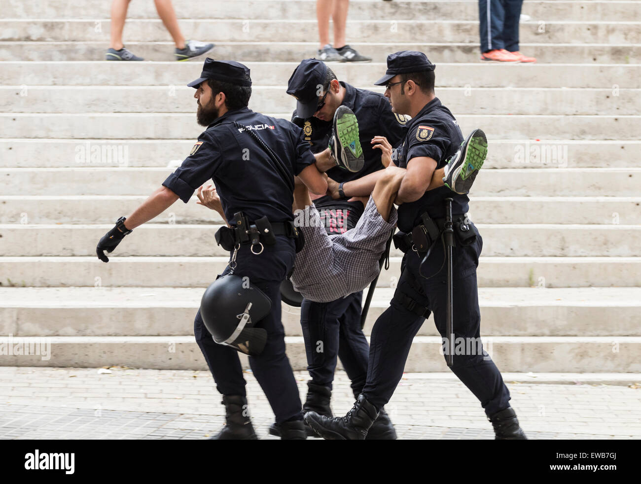 Spanish Policia Nacional (National Police) carrying a supporter during disturbance outside football stadium. - Stock Image