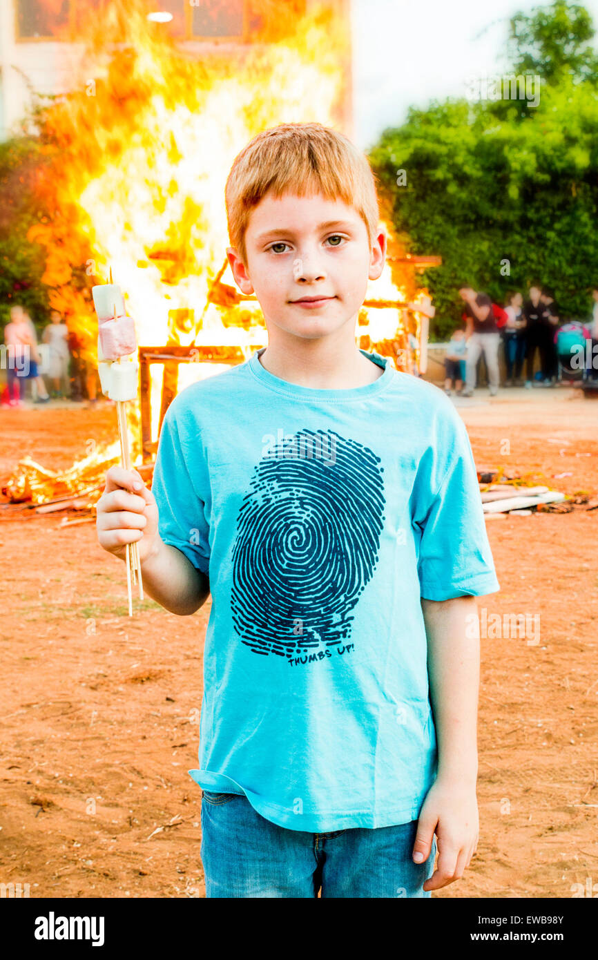 Young boy of 8 at a bonfire with marshmallows - Stock Image