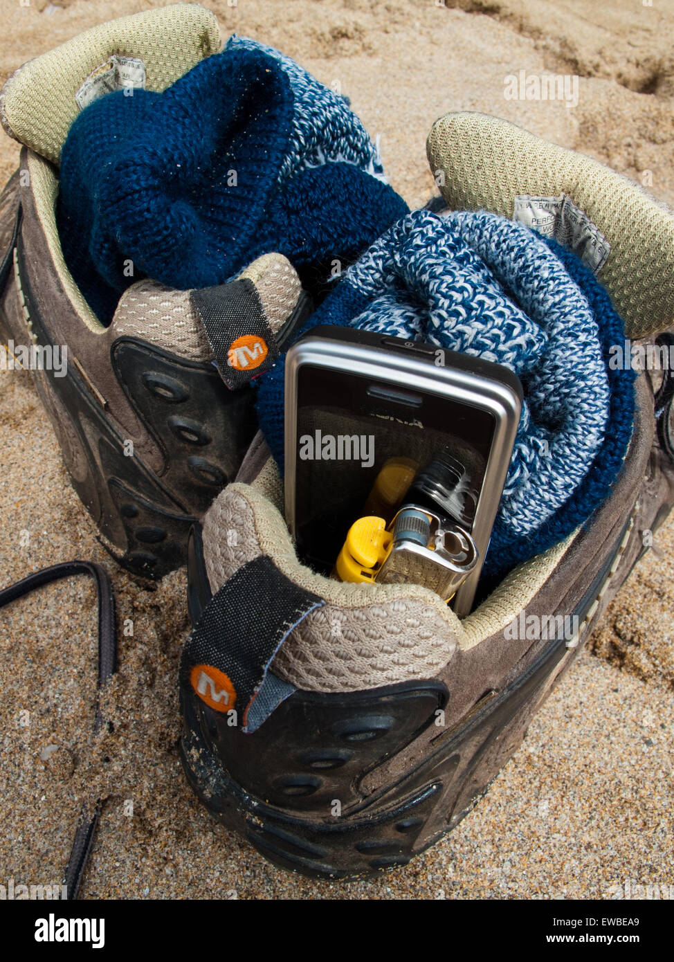 Shoes in the sand at beach, with mobile phone and cigarette lighter - Stock Image