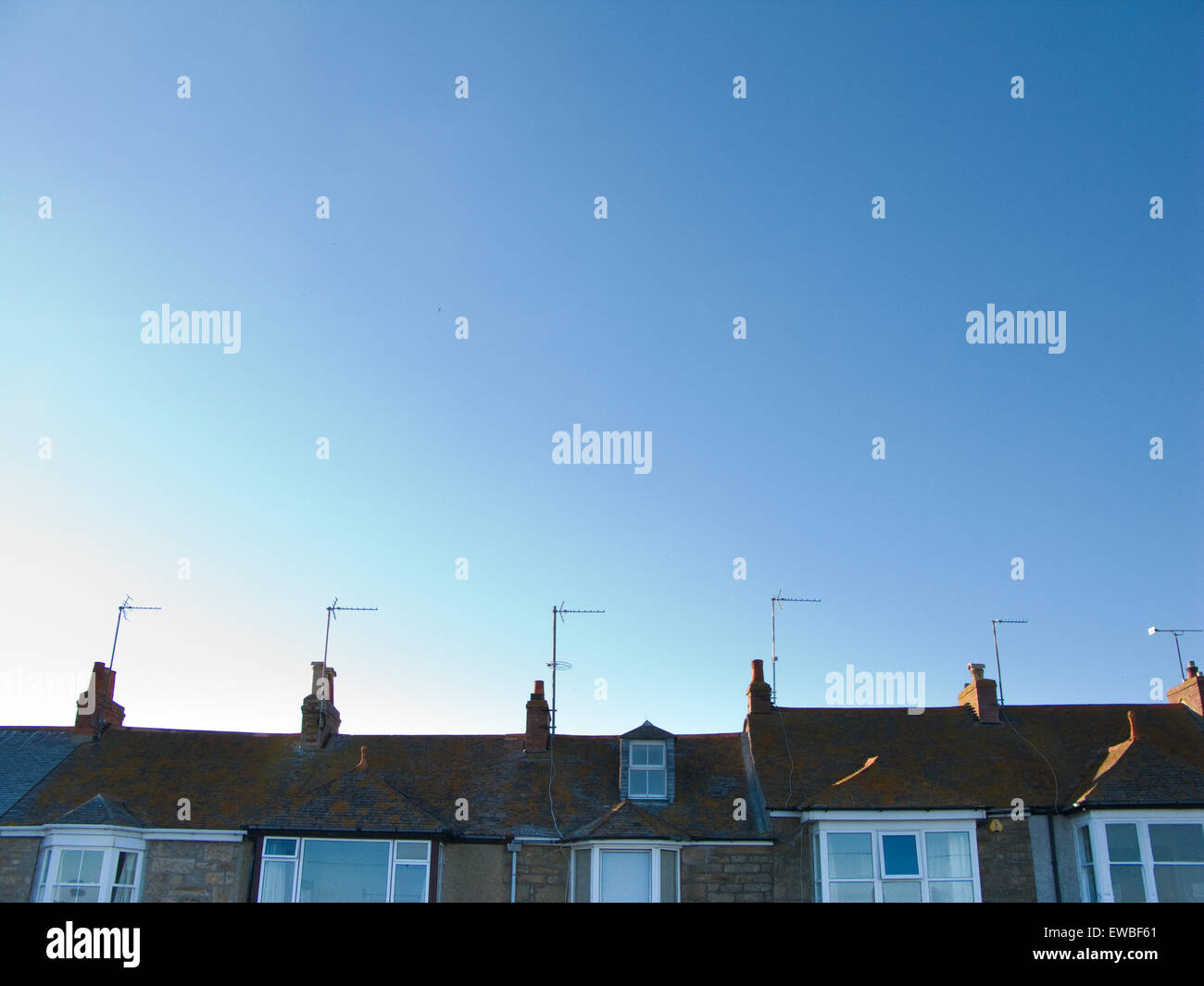 Row of terraced houses with television aerials and blue sky - Stock Image