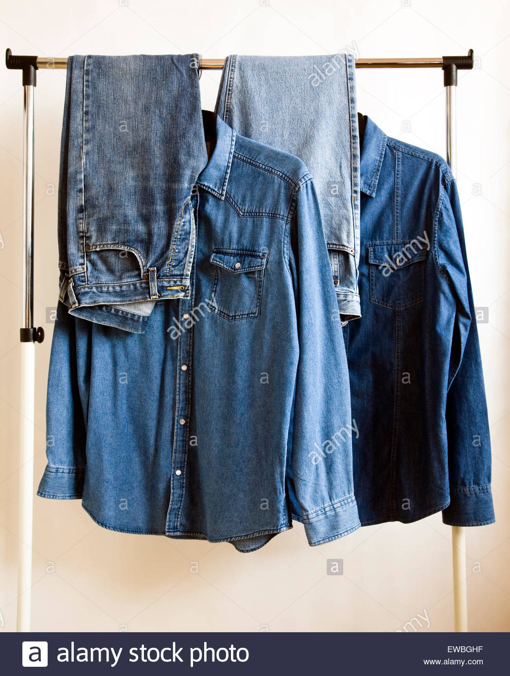 Selection of denim shirt and jeans on clothes hanging rail - Stock Image