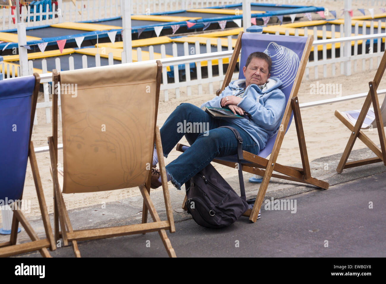 Woman snoozing in deckchair on Weymouth Esplanade in June - Stock Image