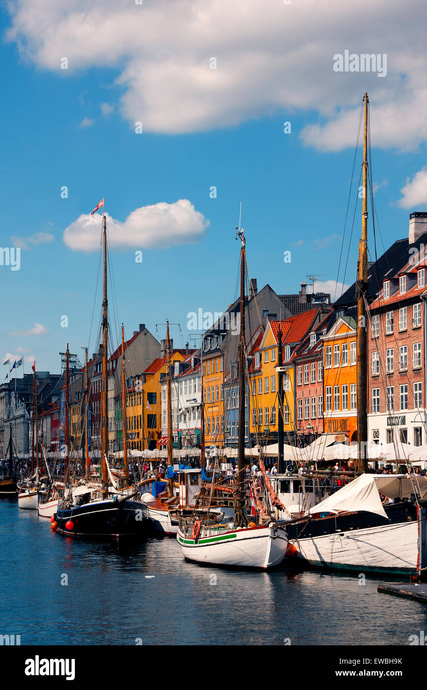 Side walk,  cafes, Townhouses and Boats along the Nyhavn Harbor in Copenhagen Denmark - Stock Image