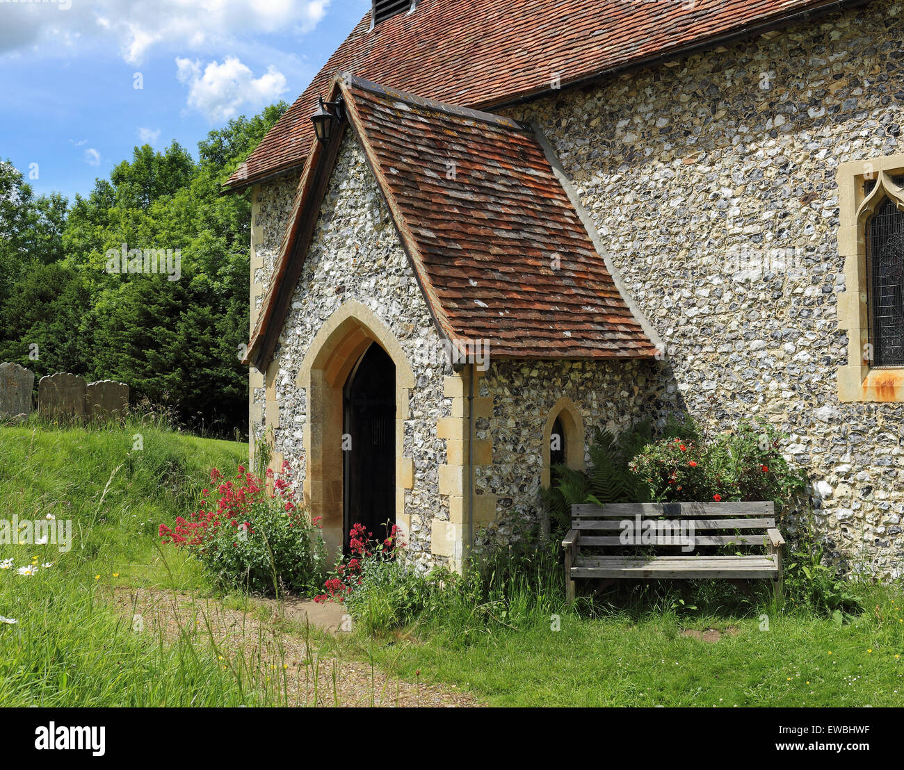 Medieval English Village Church with bench seat and flowers around the walls - Stock Image