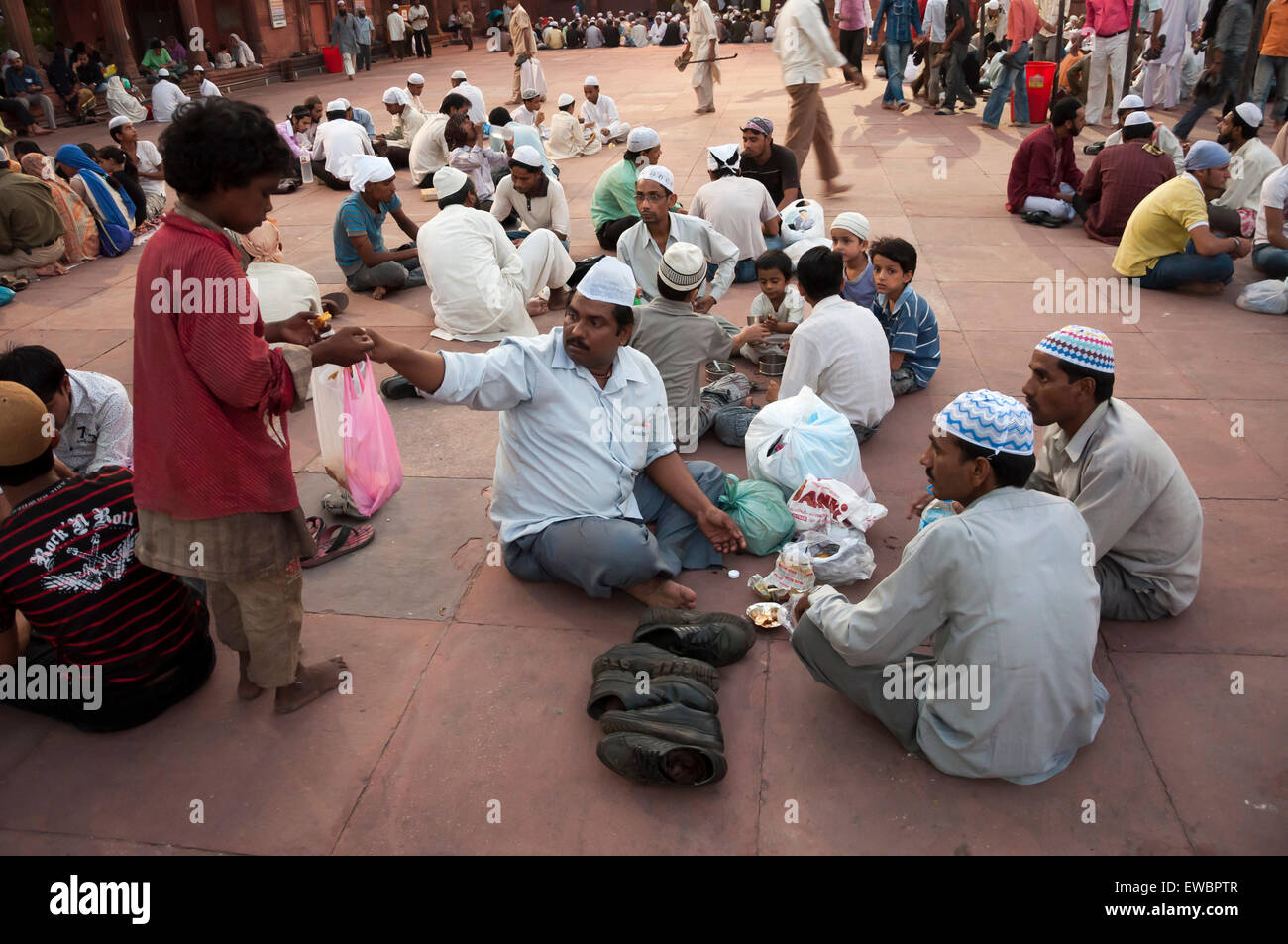 A man hands over food to a child during traditional Iftar (fast-breaking) at Jama Masjid during Ramadan. Old Delhi, - Stock Image