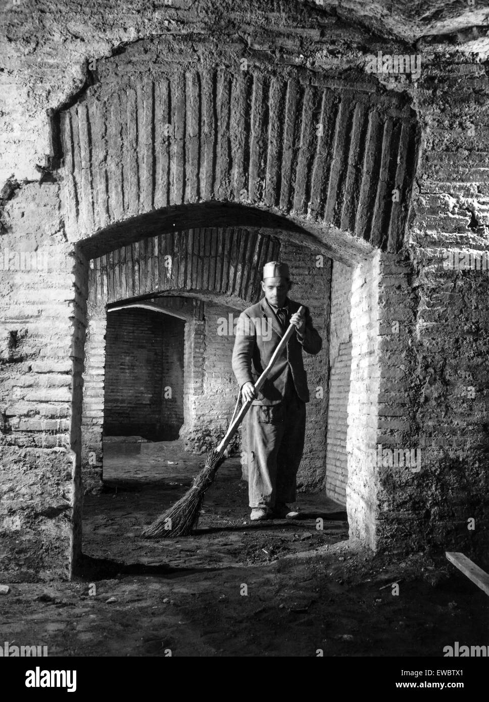 an attendant cleans the ludus magnus near the Colosseum,Rome 1960 - Stock Image