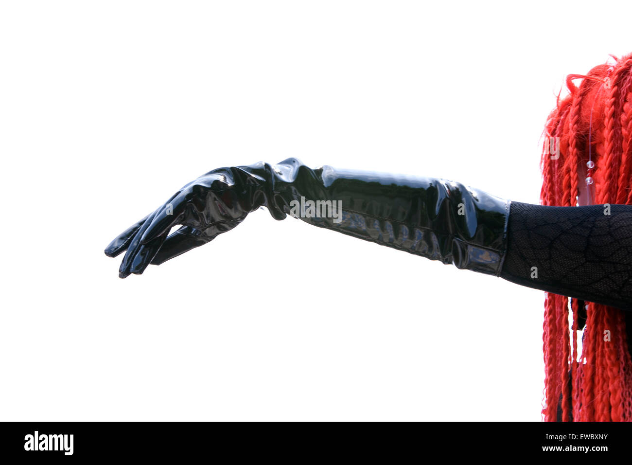 Outstretched black gloved arm and orange hair. - Stock Image