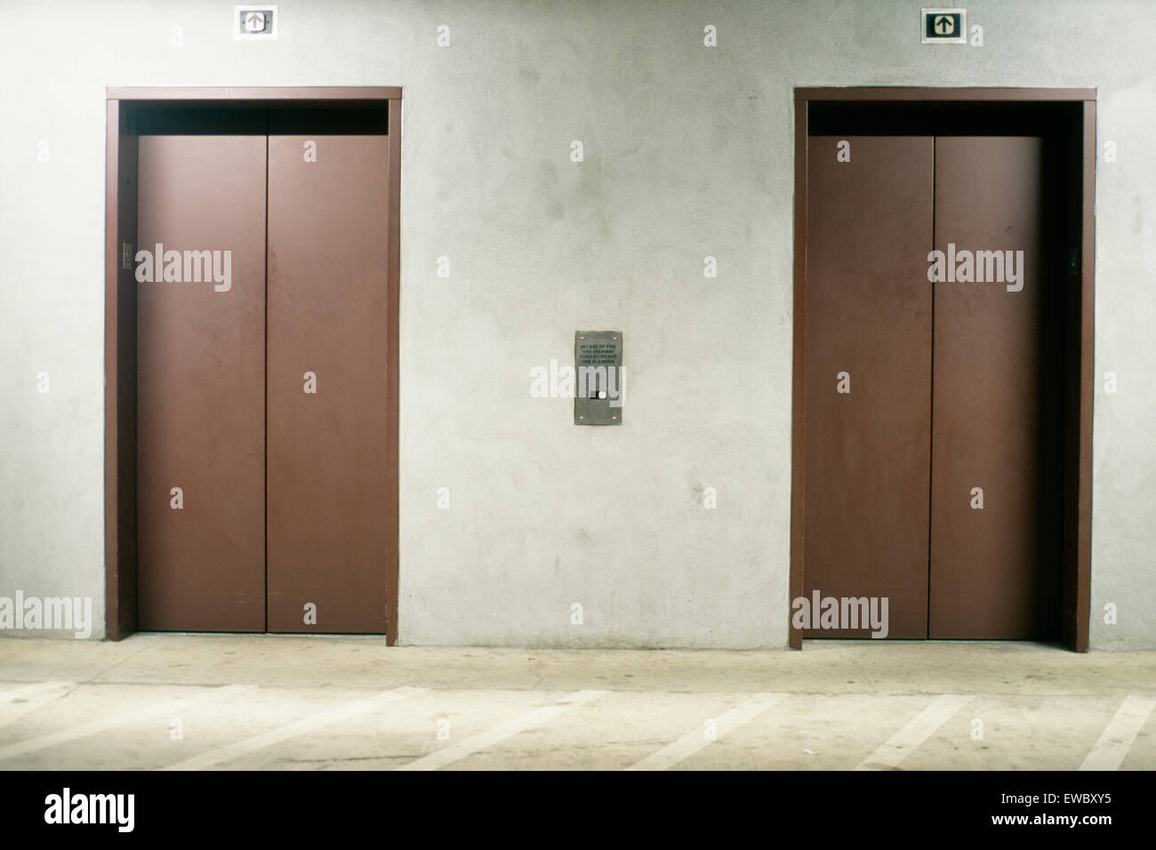 front view of two elevator doors in a underground parking garage Parking Garage Design front view of two elevator doors in a underground parking garage california
