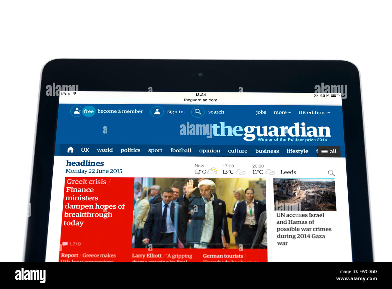 Reading the internet edition of the Guardian online newspaper on an Apple iPad Air, UK - Stock Image