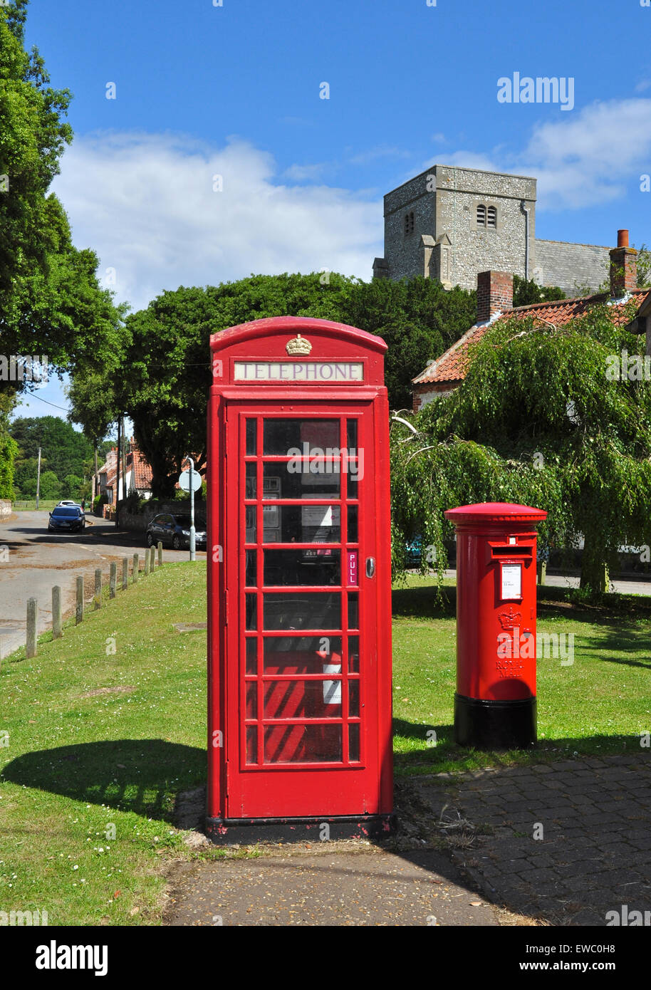 Telephone kiosk, post pillar box and church tower, Thornham, Norfolk, England, UK - Stock Image
