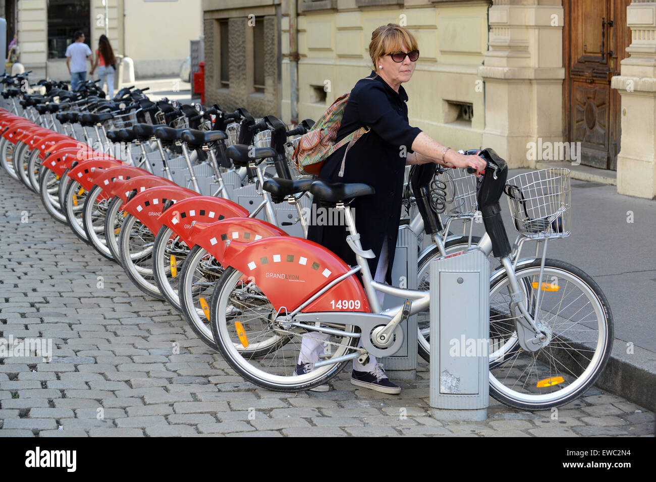 Bike hire woman hiring bicycle Lyon Burgundy France - Stock Image