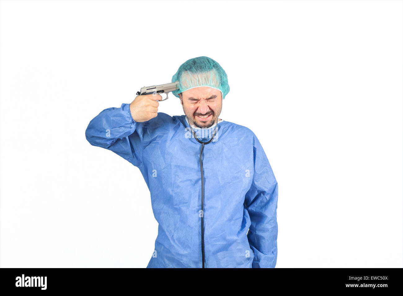 Surgeon planning to suicide, gun on his head eyes closed isolated on white background - Stock Image