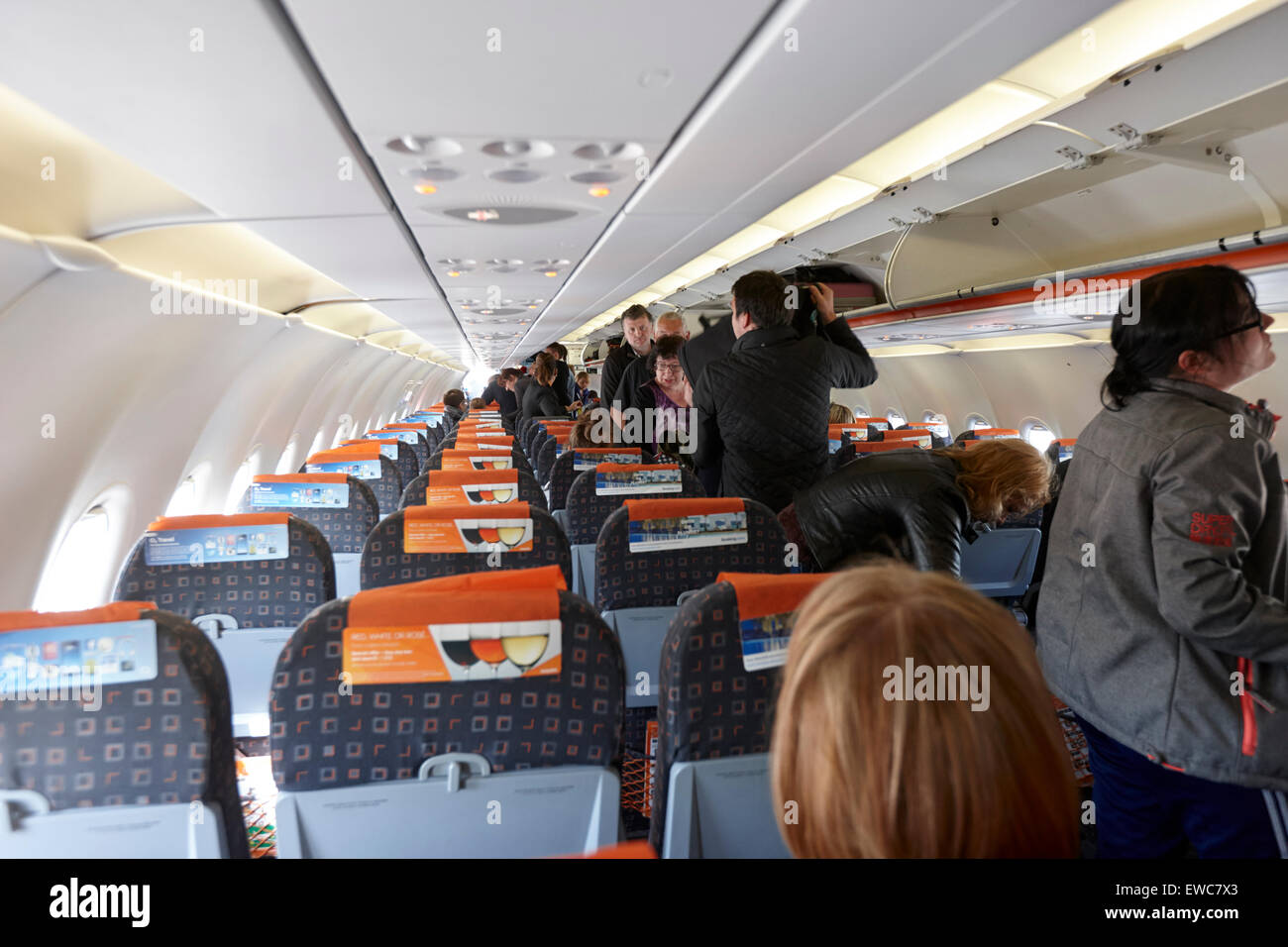 passengers place hand luggage in overhead compartments on easyjet flight Belfast International Airport UK - Stock Image