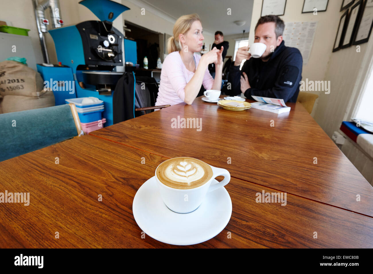 tourists sit over a coffee inside Reykjavik roasters coffee shop iceland - Stock Image
