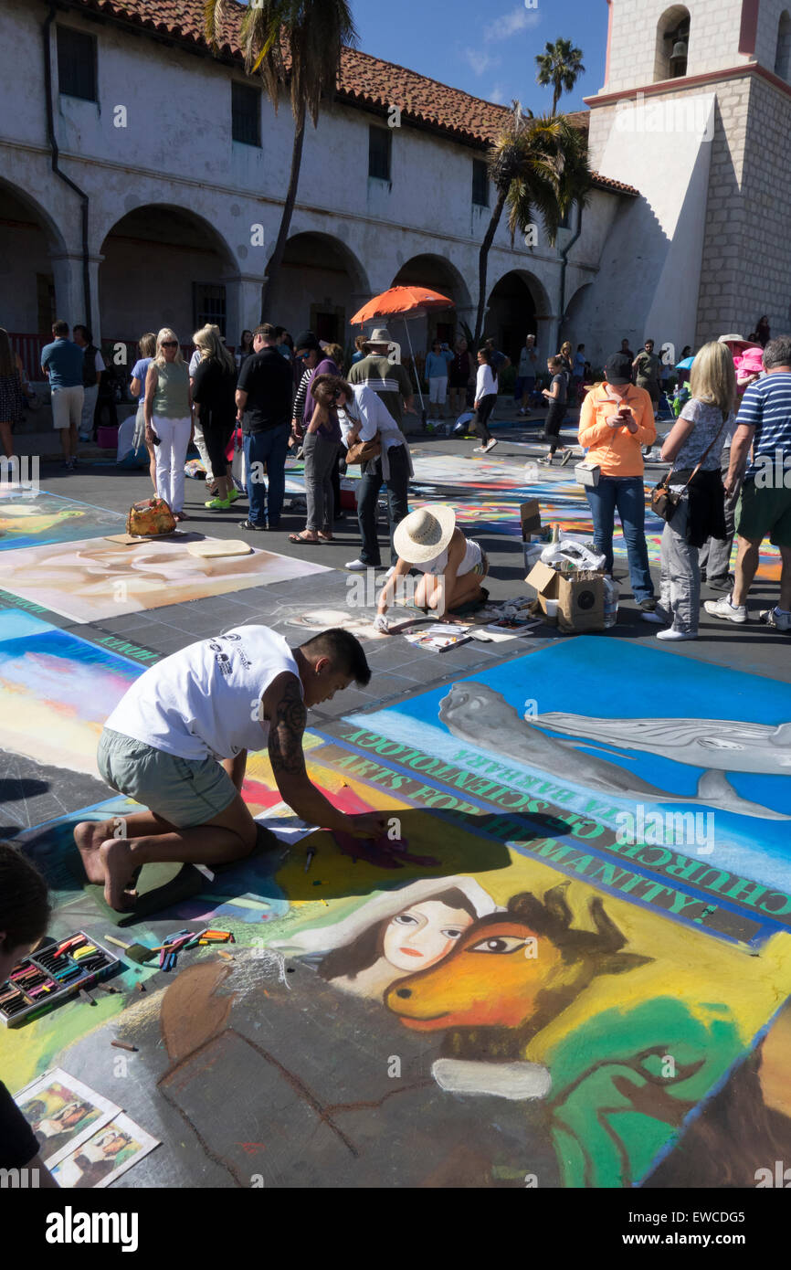 artists chalk painting on sidewalk at I Madonnari Festival in front of historic old Mission Santa Barbara Central - Stock Image