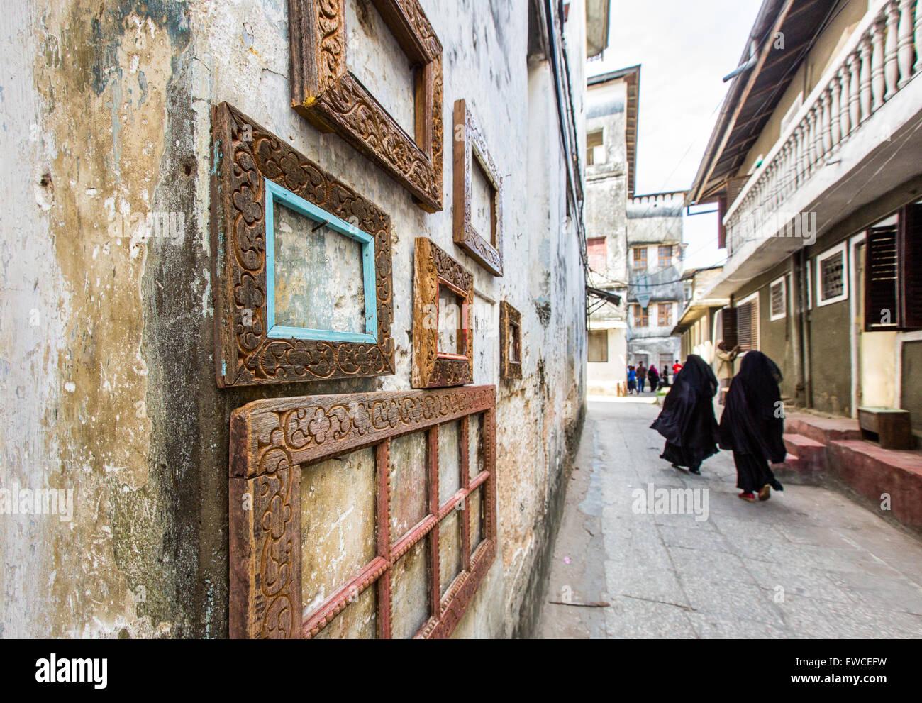 Veiled women walk past picture frames in Stone Town, Zanzibar. - Stock Image