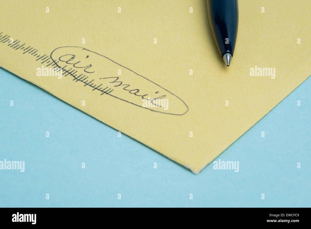 "A yellow envenlope with the words ""air mail"" written by hand in pen with the pen lying on top and a blue background. Stock Photo"